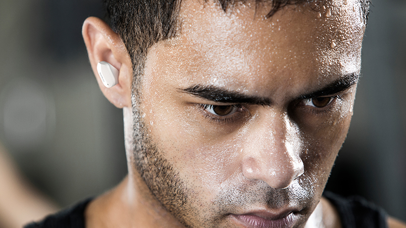 Man wearing the earbuds while working out
