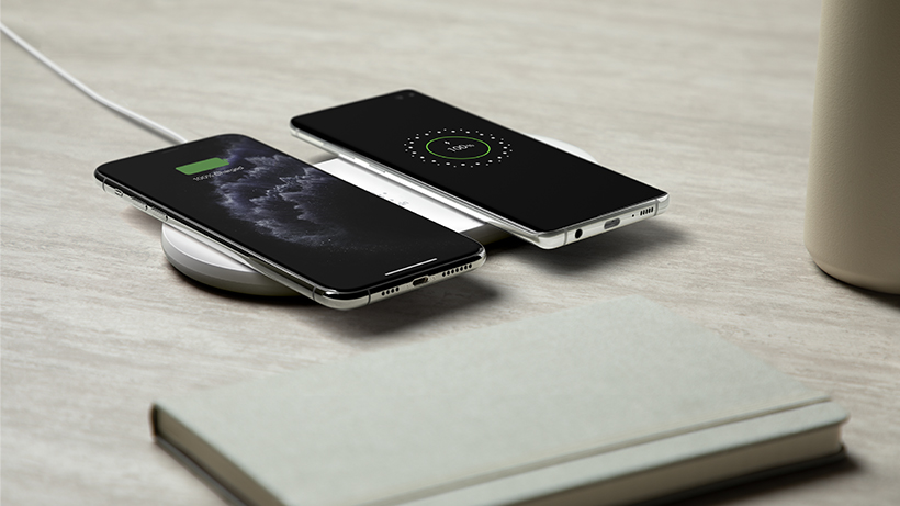 Two smartphones being charged on the BOOST↑CHARGE Dual Wireless Charging Pad