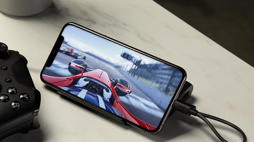 BOOST↑CHARGE Power Bank charging a smartphone with a racing game on it