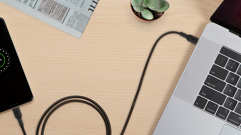 BOOST↑CHARGE braided cable plugging a smartphone into a Macbook