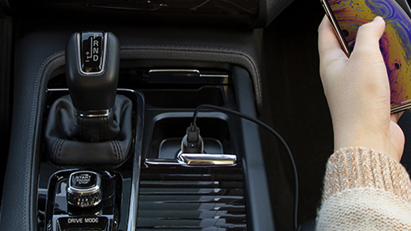 Photo of smartphone plugged into charger inside a car