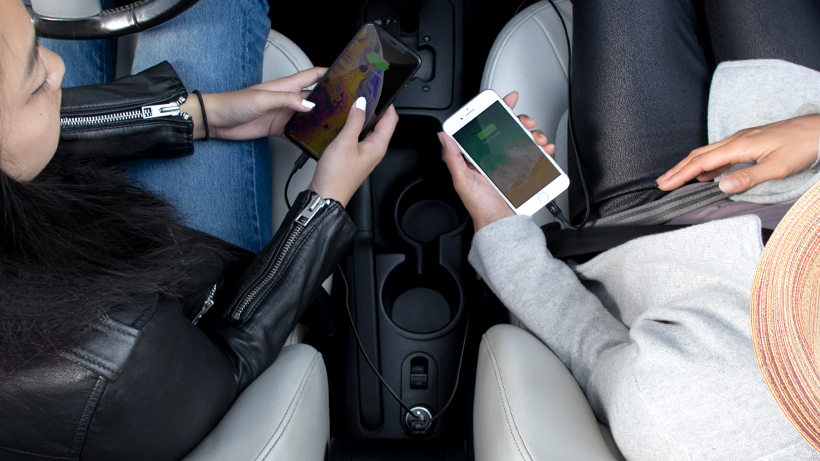 Two people charging their phones simultaneously in the car