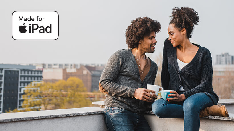 Couple sitting on a rooftop with Made for iPhone/iPad icon overlaid