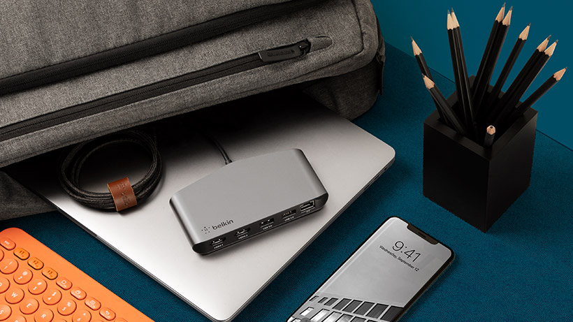 Belkin Thunderbolt™ 3 Mini Dock HD on a desk, next to a travel bag