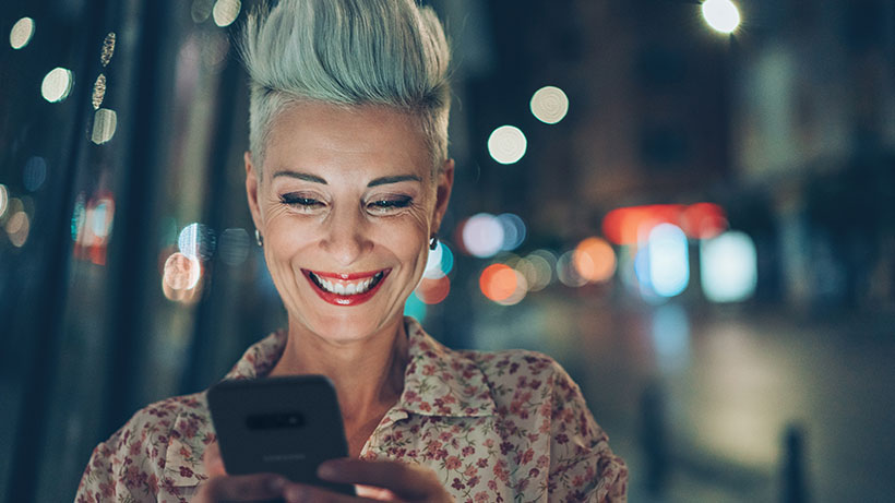 Woman smiling while texting on her phone at night