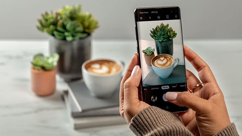 Someone taking a photo of their latte with a Samsung Galaxy S10+