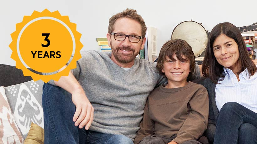 Photo with a family sitting on a couch with warranty icon overlay