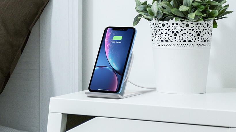 Phone charging on BOOST↑UP™ Wireless Charging Stand on a bedside table