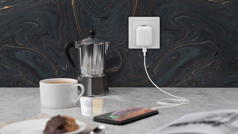 Cargador de pared BOOST↑CHARGE USB-C en una cocina suministrando corriente a un iPhone