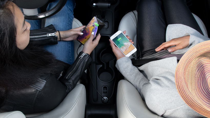 Two people charging their phones in the car simultaneously