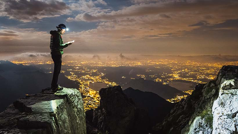 Man using iPhone on mountain top