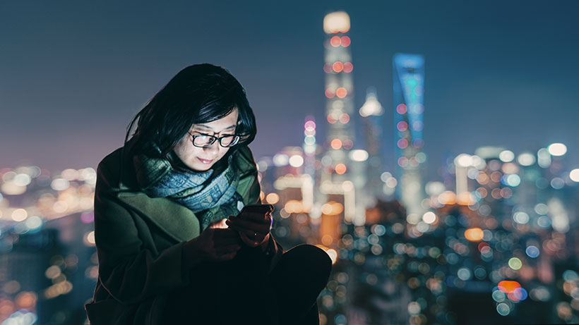 Woman using iPhone with skyline in the background