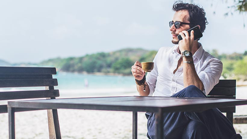 Man sitting at a table at a beach on his iPhone XS Max