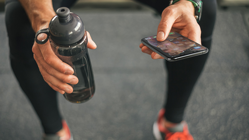 A person holding an iPhone and a water bottle