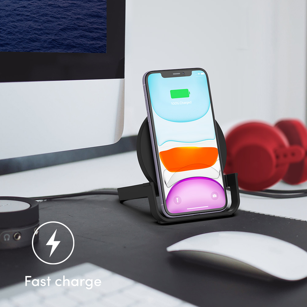 Smartphone upright on the charging pad, sitting on a desk