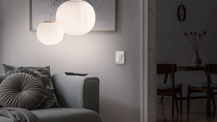 Wemo Smart WiFi Dimmer shown in living room with dimmed lighting