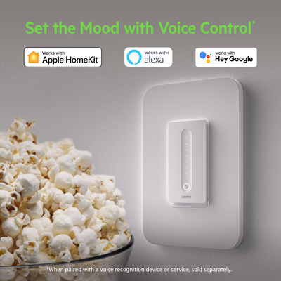 Apple HomeKit, Alexa, and Hey Google badges above Wemo Smart WiFi Dimmer and bowl of popcorn.