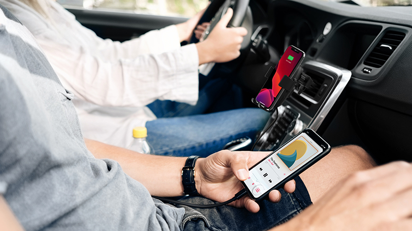 Car passenger using their smartphone while plugged in