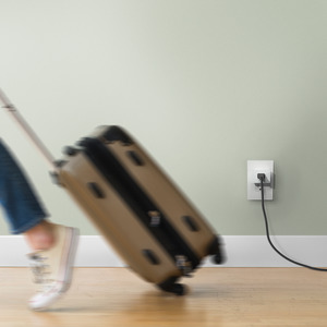 Woman with suitcase leaving her home with Wemo WiFi Smart Plug in background