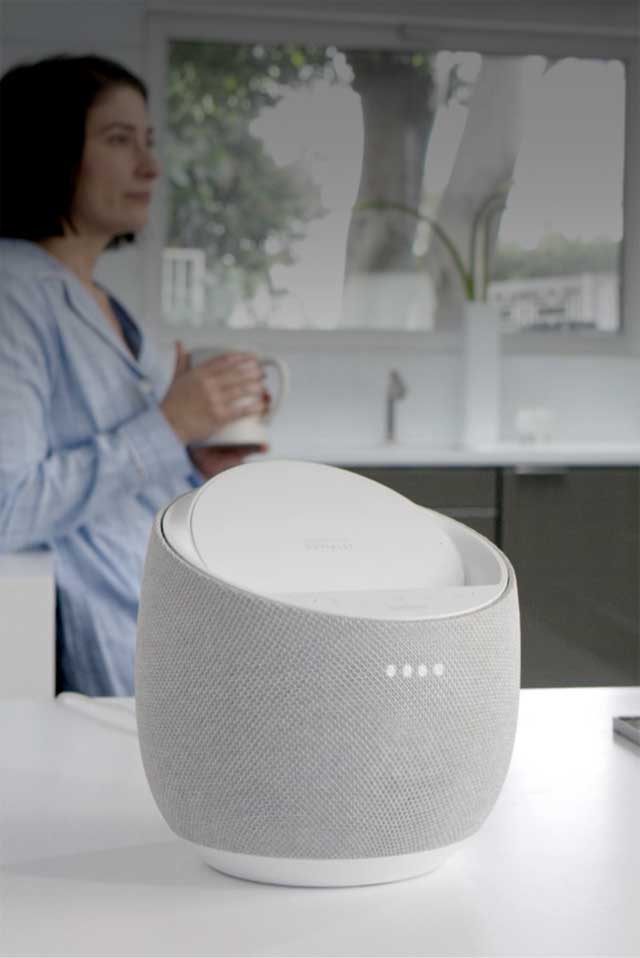 a Belkin G1S0001 Smart Speaker sits on a kitchen counter in the foreground while a person working in the kitchen speaks to the device to use the Google Assistant